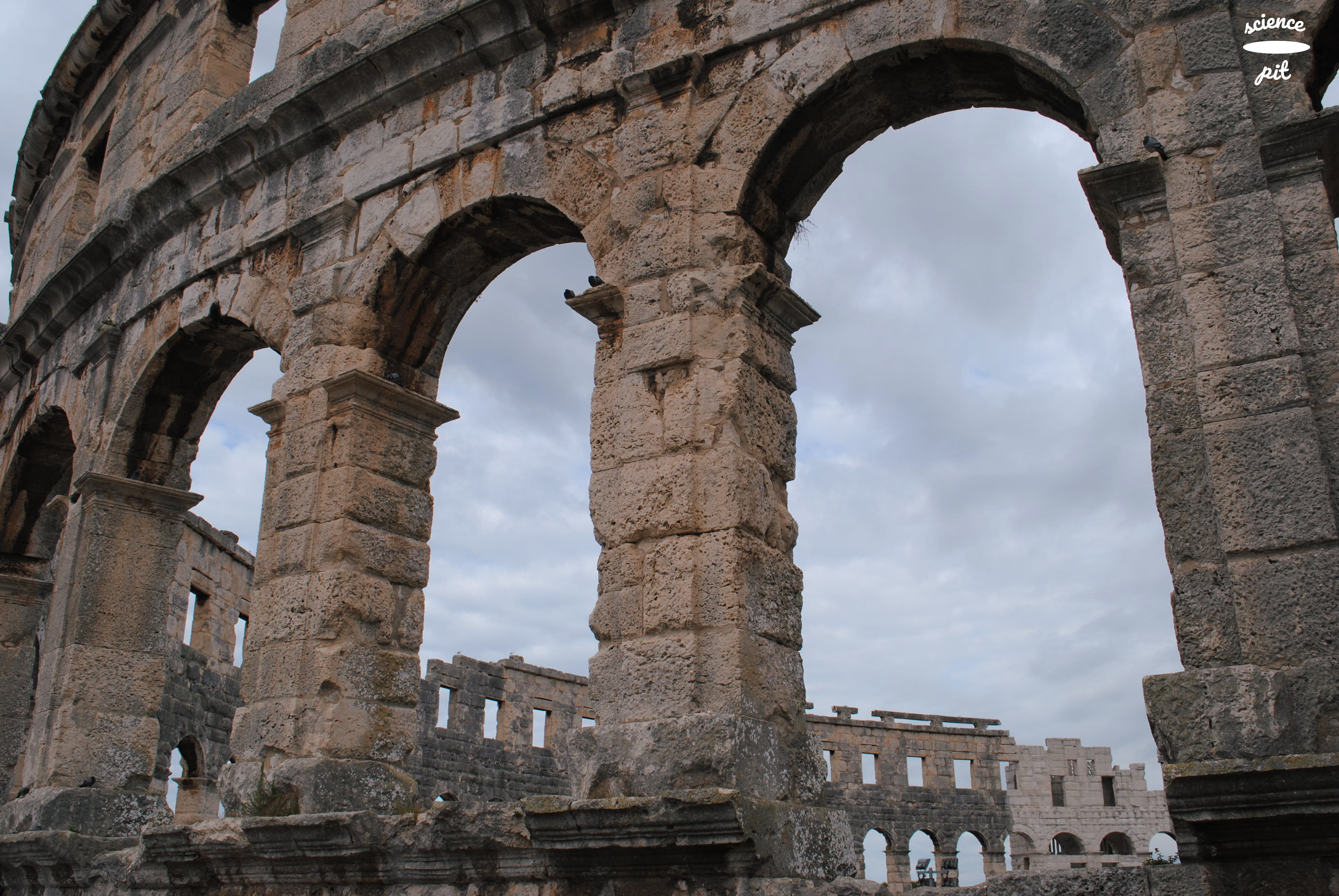 Huge stone arches of Amphitheater in Pula; with sky seen through the arches.