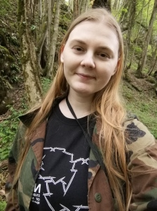 A selfie of me in the forest, wearing black shirt and a camo jacket